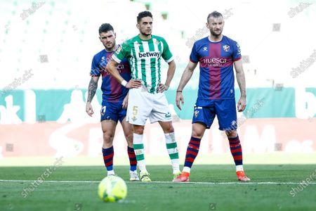 Marc Bartra of Real Betis and Javi Galan and Gaston Silva of SD Huesca