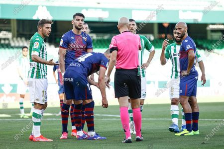 The referee Pablo Gonzalez Fuertes, Rafa Mir, Mikel Rico and Jorge Pulido of SD Huesca and Joaquin Sanchez, Guido Rodriguez and Nabil Fekir of Real Betis
