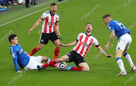 Everton's James Rodriguez, left, and Sheffield United's Chris Basham challenge for the ball during the English Premier League soccer match between Everton and Sheffield United at Goodison Park in Liverpool, England