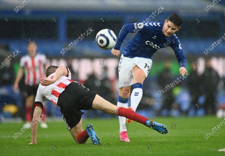 Everton's James Rodriguez, right, kicks the ball ahead of Sheffield United's Chris Basham during the English Premier League soccer match between Everton and Sheffield United at Goodison Park in Liverpool, England
