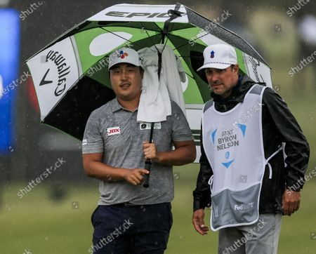 Kyoung-hoon Lee of South Korea (L) stands under an umbrella with caddie Brett Waldman (R) by the ninth green during the fourth round of the AT&T Byron Nelson golf tournament at TPC Craig Ranch in McKinney, Texas, USA, 16 May 2021. The tournament is being played 13 May through 16 May.