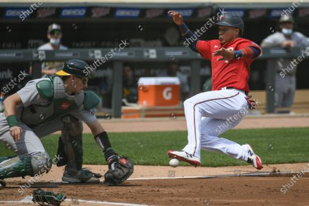 Minnesota Twins Jorge Polanco, right, slides past Oakland Athletics catcher Sean Murphy to score during the third inning of a baseball game, in Minneapolis. Originally called out by home plate umpire John Libka, Polanco was called safe after review