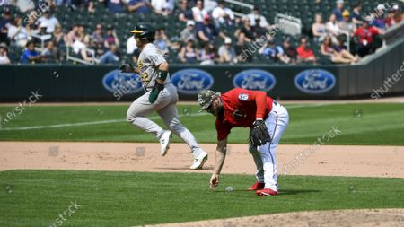 Minnesota Twins third baseman Josh Donaldson, right, mishandles a ground ball, allowing Oakland Athletics' Ramon Laureano (22) to advance to third and Seth Brown to score, during the seventh inning of a baseball game, in Minneapolis