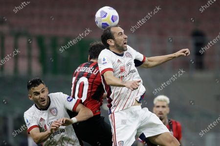 Cagliari's Diego Godin, goes for the header with AC Milan's Hakan Calhanoglu during a Serie A soccer match between AC Milan and Cagliari, at the San Siro stadium in Milan, Italy