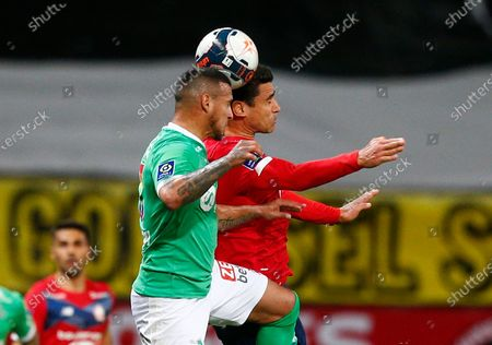 Saint-Etienne's Miguel Trauco, left vies for the ball with Lille's Benjamin Andre during the French League One soccer match between Lille and Saint-Etienne in Lille, France