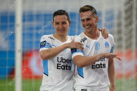 Marseille's Florian Thauvin, left, celebrates Marseille's Arkadiusz Milik's second goal after during the French League One soccer match between Marseille and Angers at the Velodrome stadium in Marseille, southern France