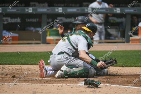 Oakland Athletics catcher Sean Murphy, front, is too late to make the tag on Minnesota Twins' Jorge Polanco whose heel crosses home plate to score during the third inning of a baseball game, in Minneapolis. Originally called out by home plate umpire John Libka, Polanco was called safe after review
