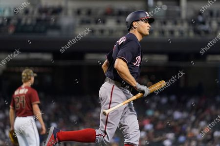 Washington Nationals' Ryan Zimmerman, right, jogs with his bat on a pop fly out against Arizona Diamondbacks starting pitcher Luke Weaver, left, during the third inning of a baseball game, in Phoenix
