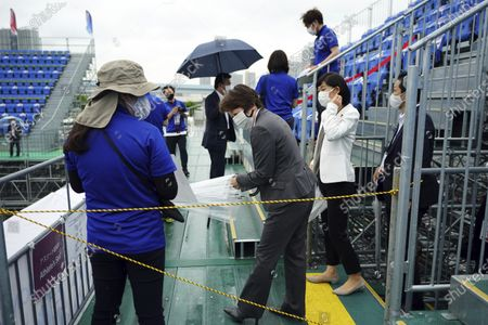 Tokyo 2020 Organizing Committee president Seiko Hashimoto, center, and Japanese Olympic Minister Tamayo Marukawa, right, arrive the grand stand in the rain to observe the Tokyo 2020 Olympic Game Cycling BMX Freestyle test event at Olympic BMX Course of Ariake Urban Sports Park in Tokyo