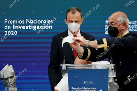 Spanish Science and Innovation Minister's Pedro Duque (C) waits as a worker disinfects the microphone at the opening of the 2020 Spanish Research Prizes awarding ceremony, at El Pardo Palace, in Madrid, Spain, 17 May 2021.