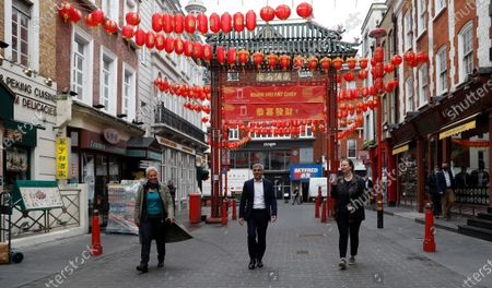 Mayor of London Sadiq Khan, centre, with chefs Angela Hartnett, right and Monica Galetti, walks in China Town central London, . Pubs and restaurants across much of the U.K. are opening for indoor service for the first time since early January even as the prime minister urged people to be cautious amid the spread of a more contagious COVID-19 variant