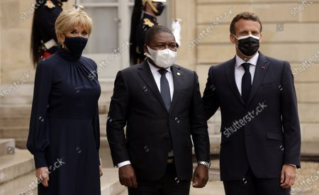 French President Emmanuel Macron (R), his wife Brigitte Macron (L) welcomes Mozambique's President Filipe Nyusi (C), before a dinner at the Elysee Palace folowing a summit on the African Economy financing in Paris, France, 17 May 2021.