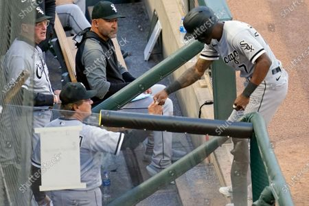 Chicago White Sox's Tim Anderson, right, is congratulated in the dugout by manager Tony La Russa after he scored on a double by Nick Madrigal off Minnesota Twins' pitcher J.A. Happ in the fourth inning of a baseball game, in Minneapolis