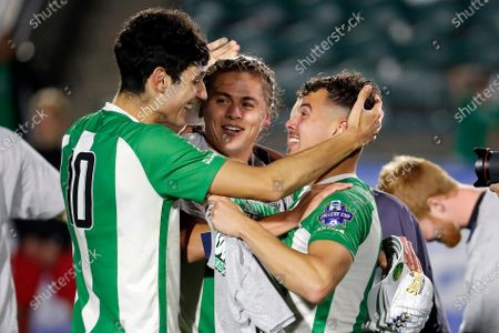Marshall's Pedro Dolabella (10), Max Schneider, center, and Jamil Roberts, right, celebrate following the team's 1-0 overtime win over Indiana at the NCAA College Cup championship soccer match in Cary, N.C
