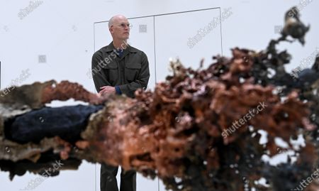 Stock Picture of U.S. artist Matthew Barney poses for photographers next to a  large scale copper, brass and stainless steel sculpture entitled 'Elk Creek Burn' during his major exhibition 'Redoubt' at the Hayward Gallery that is reopening as Covid-19 restrictions ease in London, Britain, 18 May 2021. Britain is easing some coronavirus restrictions allowing indoors locations such as pubs, museums, galleries, cinemas and adult group sports and exercise classes to reopen from 17 May. Also legal restrictions on meeting others outdoors are lifted. British Prime Minister Johnson hopes to be able to lift the majority of rules by 21 June.