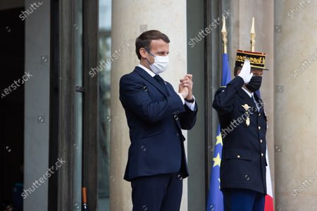 French President Emmanuel Macron waves after a meeting with the Mozambique President at the end of a meeting at the Elysee palace