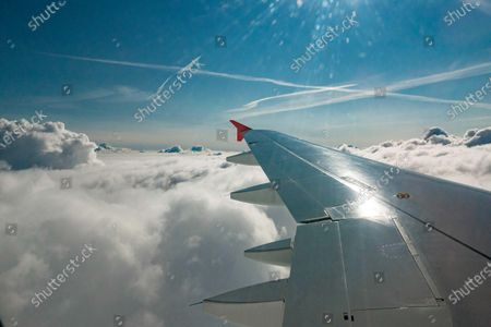 Wing view from the window of the plane with clouds during the flight. Flying with Lauda Airbus A320 airplane with registration 9H-LMJ during the Covid-19 Coronavirus pandemic with passenger and crew wearing facemask. Laudamotion or Lauda is an Austrian low-cost carrier owned by Ryanair and operating by Ryanair codes FR for IATA, RYR for ICAO and RYANAIR callsign. The budget airline carrier is based in Vienna International Airport  VIE LOWW or Flughafen Wien-Schwechat in Austria with a fleet of 28 Airbus Aircraft. Vienna, Austria on October 12, 2020