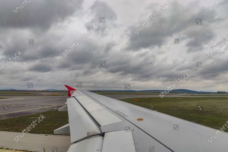 Wing view of the taxiway and runway before take off with clouds. Flying with Lauda Airbus A320 airplane with registration 9H-LMJ during the Covid-19 Coronavirus pandemic with passenger and crew wearing facemask. Laudamotion or Lauda is an Austrian low-cost carrier owned by Ryanair and operating by Ryanair codes FR for IATA, RYR for ICAO and RYANAIR callsign. The budget airline carrier is based in Vienna International Airport  VIE LOWW or Flughafen Wien-Schwechat in Austria with a fleet of 28 Airbus Aircraft. Vienna, Austria on October 12, 2020