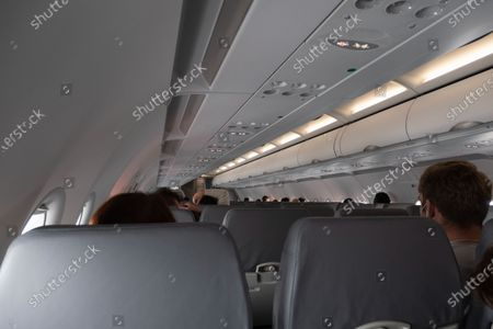 Interior of the cabin during the flight. Flying with Lauda Airbus A320 airplane with registration 9H-LMJ during the Covid-19 Coronavirus pandemic with passenger and crew wearing facemask. Laudamotion or Lauda is an Austrian low-cost carrier owned by Ryanair and operating by Ryanair codes FR for IATA, RYR for ICAO and RYANAIR callsign. The budget airline carrier is based in Vienna International Airport  VIE LOWW or Flughafen Wien-Schwechat in Austria with a fleet of 28 Airbus Aircraft. Vienna, Austria on October 12, 2020
