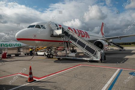 Stock Image of The plane parked at the destination airport. Flying with Lauda Airbus A320 airplane with registration 9H-LMJ during the Covid-19 Coronavirus pandemic with passenger and crew wearing facemask. Laudamotion or Lauda is an Austrian low-cost carrier owned by Ryanair and operating by Ryanair codes FR for IATA, RYR for ICAO and RYANAIR callsign. The budget airline carrier is based in Vienna International Airport  VIE LOWW or Flughafen Wien-Schwechat in Austria with a fleet of 28 Airbus Aircraft. Vienna, Austria on October 12, 2020