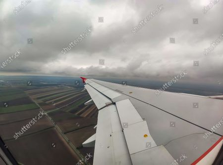 Wing view from the window of the plane with clouds and Austrian fields during the flight. Flying with Lauda Airbus A320 airplane with registration 9H-LMJ during the Covid-19 Coronavirus pandemic with passenger and crew wearing facemask. Laudamotion or Lauda is an Austrian low-cost carrier owned by Ryanair and operating by Ryanair codes FR for IATA, RYR for ICAO and RYANAIR callsign. The budget airline carrier is based in Vienna International Airport  VIE LOWW or Flughafen Wien-Schwechat in Austria with a fleet of 28 Airbus Aircraft. Vienna, Austria on October 12, 2020