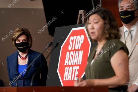House Speaker Nancy Pelosi of Calif., left, listens as Rep. Grace Meng, D-N.Y., center, speaks during a news conference on Capitol Hill in Washington, on the COVID-19 Hate Crimes Act. Rep. Mark Takano, D-Calif., listens at right