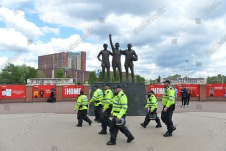Stock Image of Police officers patrol past the statue outside Old Trafford stadium depicting the former players George Best, Denis Law and Sir Bobby Charlton, ahead of the English Premier League soccer match between Manchester United and Fulham FC in Manchester, Britain, 18 May 2021.