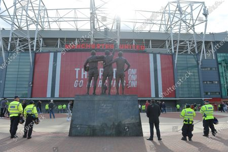 Police officers stand guard next to the statue outside Old Trafford stadium depicting the former players George Best, Denis Law and Sir Bobby Charlton, ahead of the English Premier League soccer match between Manchester United and Fulham FC in Manchester, Britain, 18 May 2021.