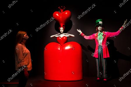 A member of staff stands next to models and costumes by Bob Crowley of the 'Queen of Hearts' and 'Mad Hatter' characters on display in the exhibition 'Alice: Curiouser and Curiouser' at the Victoria and Albert Museum in London, Britain, 18 May 2021. The exhibition is designed by award-winning designerTomPiper and runs from 22 May to 31 December 2021.