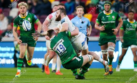 Luke Cowan-Dickie of Exeter passes as he's  tackled by George Nott of London Irish
