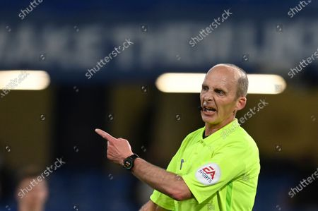 Referee Mike Dean gestures during the English Premier League soccer match between Chelsea and Leicester City at Stamford Bridge Stadium in London
