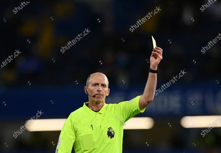 Referee Mike Dean shows a yellow card during the English Premier League soccer match between Chelsea and Leicester City at Stamford Bridge Stadium in London