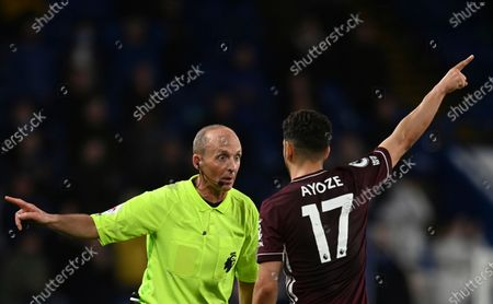 Referee Mike Dean, left, discusses with Leicester's Ayoze Perez during the English Premier League soccer match between Chelsea and Leicester City at Stamford Bridge Stadium in London