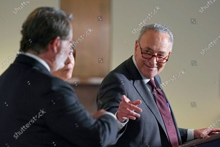 Senate Majority Leader Chuck Schumer of N.Y., right, speaks on Capitol Hill in Washington, . He is joined by Sen. Gary Peters., D-Mich., left, and Sen. Maria Cantwell, D-Wash., center