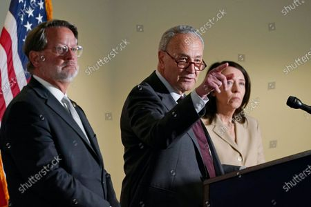 Senate Majority Leader Chuck Schumer of N.Y., center, speaks on Capitol Hill in Washington, . He is joined by Sen. Gary Peters., D-Mich., left, and Sen. Maria Cantwell, D-Wash., right