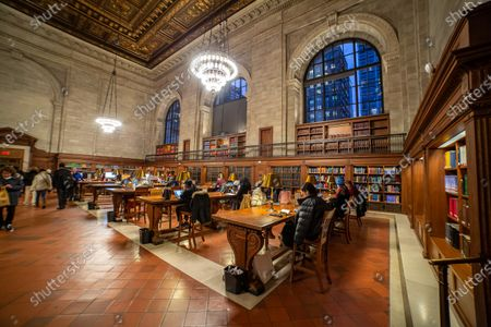 Inside the Rose Main Reading Room, the main reading room with side books and large windows, officially Room 315 on the third floor, a room 78 x 297 feet and 52 foot high wooden carved ceiling in a style between Renaissance architectural style and Beaux-Arts design in the Stephen A. Schwarzman Building, commonly known as the Main Branch. New York Public Library Main Branch in Bryant Park, Manhattan, NYPL, is the third largest library in the world. The branch was declared a National Historic Landmark in 1965 and designated a New York City Landmark in 1967. The research library was opened to public on May 23, 1911, built by the architect Carrere and Hastings on the Fifth Avenue, nowaday is a landmark, a monument for locals and attraction to tourists with thousands of daily visitors, as it become famous after appearing in movies and tv shows.  On 23 January 2020 in NYC, USA.