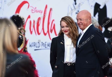 """Emma Stone, left, and Disney CEO Bob Chapek appear on the red carpet as they arrive at the premiere of """"Cruella"""" at the El Capitan Theatre, in Los Angeles"""