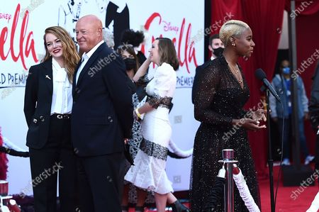 """Emma Stone, from left, Disney CEO Bob Chapek and Kirby Howell-Baptiste appear on the red carpet as they arrive at the premiere of """"Cruella"""" at the El Capitan Theatre, in Los Angeles"""