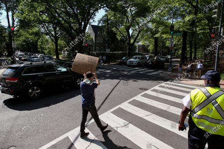 Stock Image of Jonathan Tucker of Washington, D.C. holds a sign alongside traffic during a protest outside of the Embassy of Israel on May 18, 2021