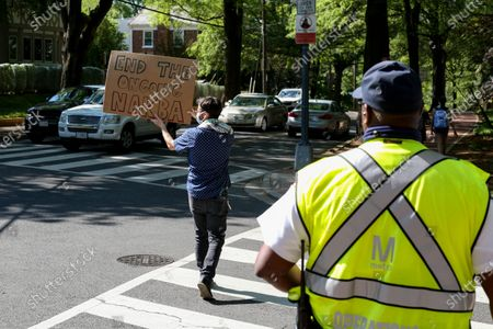 Jonathan Tucker of Washington, D.C. holds a sign alongside traffic during a protest outside of the Embassy of Israel on May 18, 2021