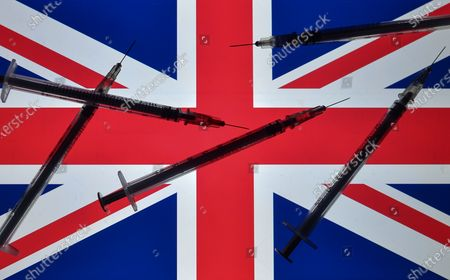 An illustrative photo showing medical syringes seen in front of the national flag of the United Kingdom displayed on a screen in the background on Christmas Eve.On Thursday, December 24, 2020, in Dublin, Ireland. (Photo illustration by Artur Widak/NurPhoto)