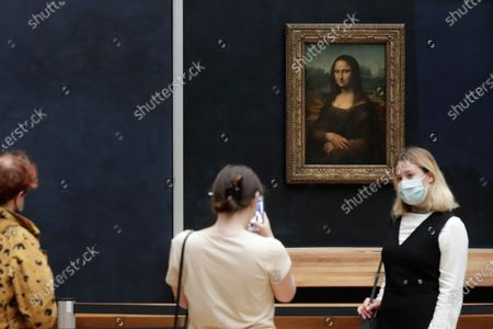 Stock Picture of Visitors pose in front of Leonardo da Vinci's Mona Lisa in the Louvre museum, in Paris. Museums must restrict entries so there is 8 square meters of space (86 square feet) per visitor. Café and restaurant terraces are reopening Wednesday after a shutdown of more than six months deprived people of what feels like the essence of life - sipping coffee and wine with friends outdoors - to save lives during the coronavirus pandemic