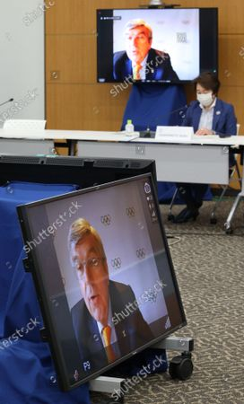 International Olympic Committee (IOC) president Thomas Bach delivers an opening speech on a screen at a meeting of the IOC Coordination Commission for the Tokyo 2020 Olympics in Tokyo, while Tokyo 2020 Olympics organizing committee president Seiko Hashimoto listens to May 19, 2021. IOC President Thomas Bach, Tokyo 2020 organizing committee president Seiko Hashimoto, Japanese Olympic Minister Tamayo Marukawa and Tokyo Governor Yuriko Koike attended a three-day meeting.
