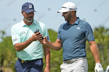 Dustin Johnson, right, has his phone to Matt Kuchar on the 11th hole during a practice round at the PGA Championship golf tournament on the Ocean Course, in Kiawah Island, S.C