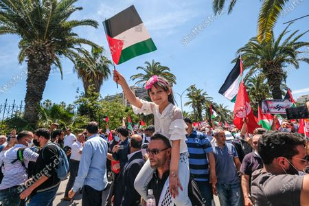 A man carry a young girl on his shoulders.  Tunisian Genral Labour union (UGTT) called for protest to support palestinians after the latest israeli attacks on Gza strip and Sheikh JArrah neighbourhood.