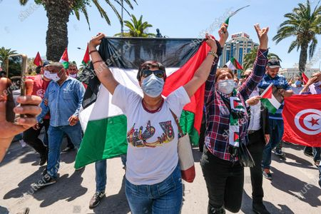 Stock Image of A woman carries the palestinian flag. Tunisian Genral Labour union (UGTT) called for protest to support palestinians after the latest israeli attacks on Gza strip and Sheikh JArrah neighbourhood.