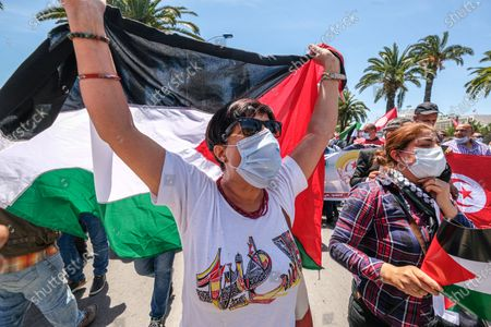 A woman carries the palestinian flag. Tunisian Genral Labour union (UGTT) called for protest to support palestinians after the latest israeli attacks on Gza strip and Sheikh JArrah neighbourhood.