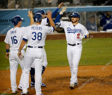 Los Angeles Dodgers Gavin Lux (9) is congratulated by teammates Chris Taylor (3), Will Smith (16) and DJ Peters (38) after hitting a grand slam home run off Arizona Diamondbacks relief pitcher Kevin Ginkel (37) putting the Dodgers up 8-1 in the seventh inning at Dodger Stadium on Tuesday, May 18, 2021 in Los Angeles, CA. (Gary Coronado / Los Angeles Times)