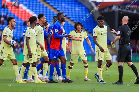 Crystal Palace #20 forward Christian Benteke yellow card by Referee Anthony Taylor and Arsenal midfielder Mohamed Elneny (25) during the Premier League match between Crystal Palace and Arsenal at Selhurst Park, London