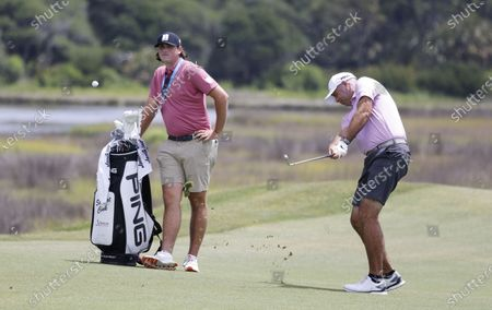 Stewart Cink of the US (R) and his son and caddie Reagan (L) as he hits from the fairway on the tenth hole during the final practice round for the 2021 PGA Championship golf tournament on the Ocean Course at Kiawah Island, South Carolina, USA, 18 May 2021. The PGA Championship runs from 20 May through 23 May.